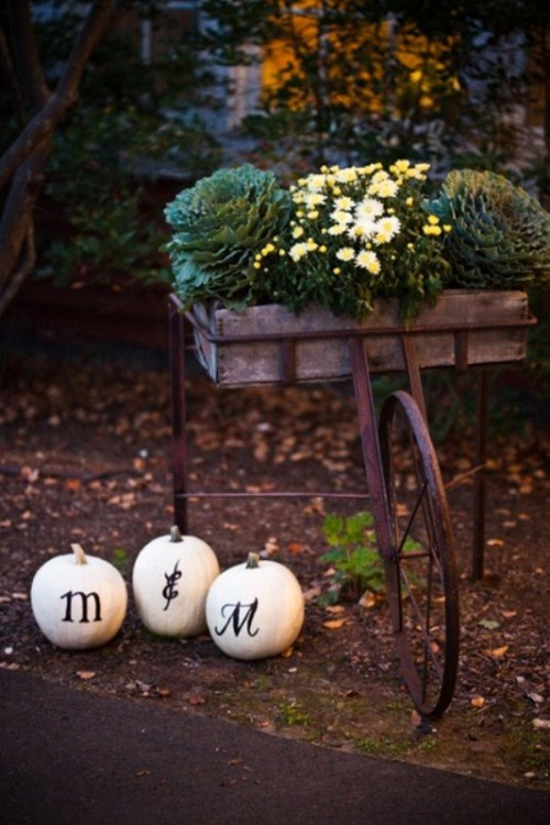 a cart with cabbages and white blooms and white pumpkins for decorating a wedding reception or ceremony space