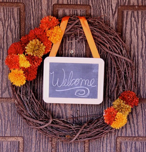 "Add some fall blooms to a bunch of grapevine twigs. A chalkboard ""welcome"" sign is totally optional."