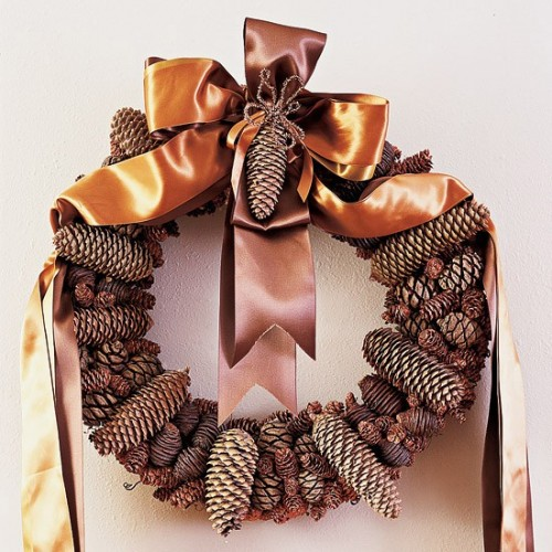 Spray paint a straw wreath in brown. and attach pinecones to it using a hot glue gun. To add a festive touch use golden ribbon to hang the wreath on a door.