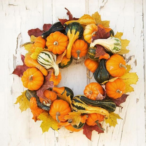 DIY pumpkin wreath would be a great piece of decor for your entryway.  The most popular symbol of fall would look great on dark doors.