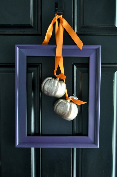 For a super minimalist fall wreath  take a vintage frame and hang several tiny  pumpkins on it using ribbon.