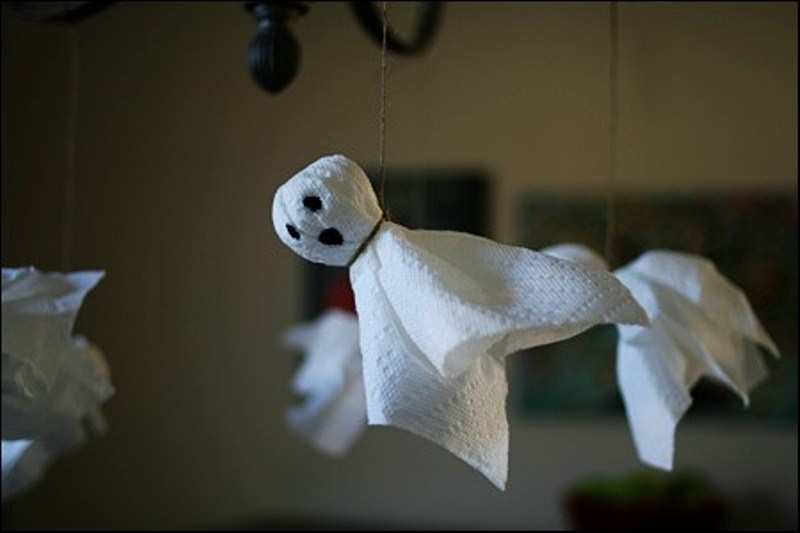 funny napkin ghosts hanging on a chandelier can be an easy craft for Halloween that even your kids can make