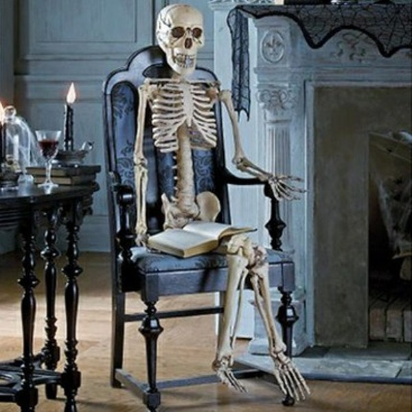 a skeleton in a vintage black chair is a stylish and refined idea of Halloween decor that is easy to make