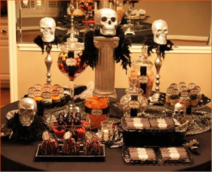a Halloween decoration of skulls and feathers doubles as a stand for sweets for a Halloween party