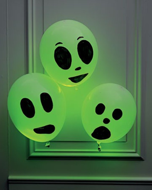 easy ghosts of balloons with scary faces in green are nice decorations for Halloween, they can be used instead of wreaths