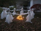 cheesecloth ghosts reeling around a fire are a scary and cool Halloween decoration for outdoors