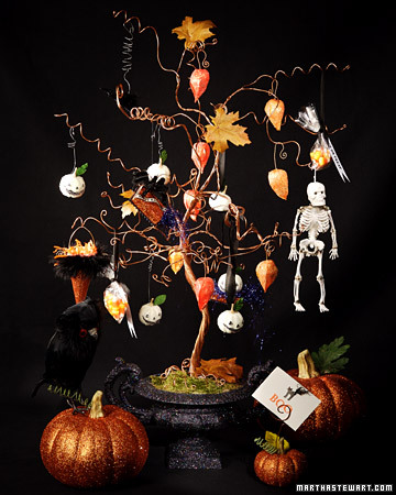 an orange Halloween tree in a black urn with moss, with dried blooms, toy skeletons and Halloween lanterns on it