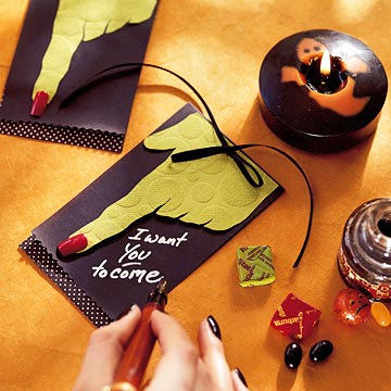 a black Halloween invitation with a monster hand and a bow is a cool bold idea