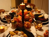 faux pumpkins and candles in tall candleholders will fit a stylish rustic Halloween tablescape