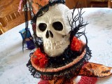 a stand with lace and faux red blooms, a white patterned skull, scary branches and a witch hat on top