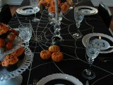 orange roses in a vase, a mummy candle and orange mini pumpkins for Halloween table decor