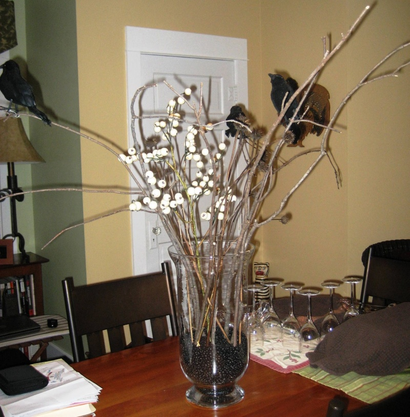 a vase with branches, berries, blackbirds and black beads in the vase is an easy last minute Halloween centerpiece