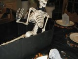 a coffin with a skeleton in a hat is a unique Halloween centerpiece that you may boldly rock at the party