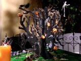 a black cardboard tree with pumpkins, blackbirds, skeletons and hay is a creative Halloween decoration or centerpiece