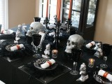 a black candelabra with orange candles and elegant skulls is a stylish and refined Halloween centerpiece