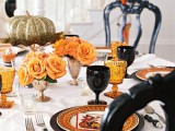 a gilded pumpkin on moss and a stand, orange roses in goblets are lovely for Halloween table styling