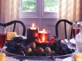 a decadent Halloween centerpiece of a bowl with grapes, blackberries, pears, apples and dark candles is very refined
