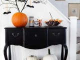 black branches inserted into a large pumpkin and decorated with black paper bats is a cool Halloween tree