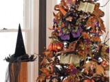 a black lit up Halloween tree decorated with leaves, glitter pumpkins, witches' hats and boots