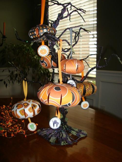 a black Halloween tree decorated with orange paper pumpkins on a stand is a bold and dramatic decoration