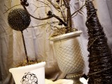 grey and black branches in a neutral vase, with black ornaments and beads glued to the branches