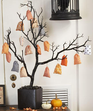 a black tree in a black urn, with colorful fabric sacks with mini favors is a fun idea for Halloween