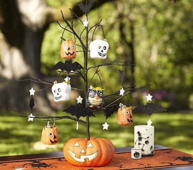 a black Halloween tree inserted into a pumpkin, with orange and white pumpkins and stars and owls for decor