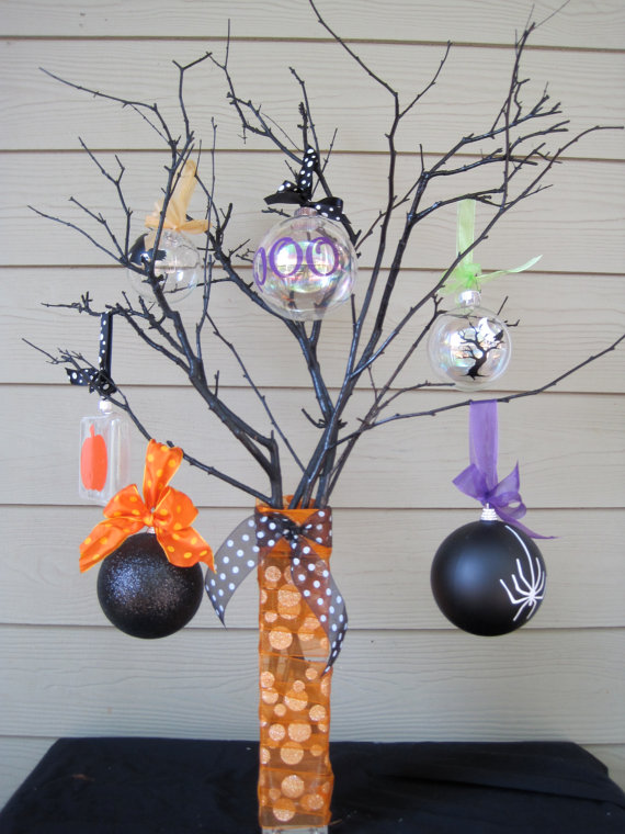 black branches placed in a vase wrapped with orange ribbons, with black and sheer glass ornaments and colorful ribbons