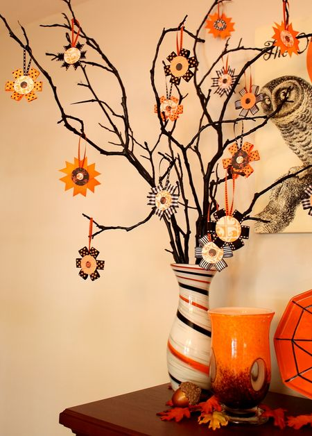 black branches in a striped vase, with colorful paper ornaments is a creative and easy idea of a Halloween tree