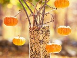 non-painted branches placed into a vase with seeds and with mini pumpkins as ornaments is very natural and cool