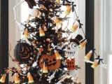 a black Halloween tree with twigs, lights, candy corns, glitter orange and black pumpkins and Jack Skellington