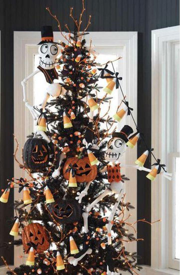 a black Halloween tree with twigs, lights, candy corns, glitter orange and black pumpkins and Jack Skellington