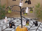 a black Halloween tree decorated white, green and black glitter lanterns and inserted into a pumpkin
