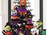 a black Halloween tree with colorful jack-o-lantern toys in purple, green, orange and white for Halloween