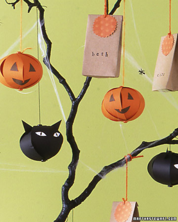 black branches with black cat heads and orange pumpkins of paper hanging and paper bags for a Halloween tree