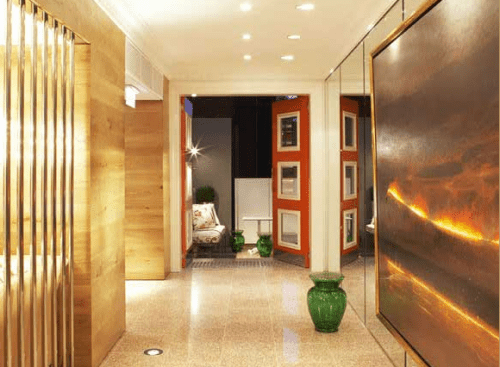 Oversized art, natural wood and red doors make this hallway's design truly memorable.