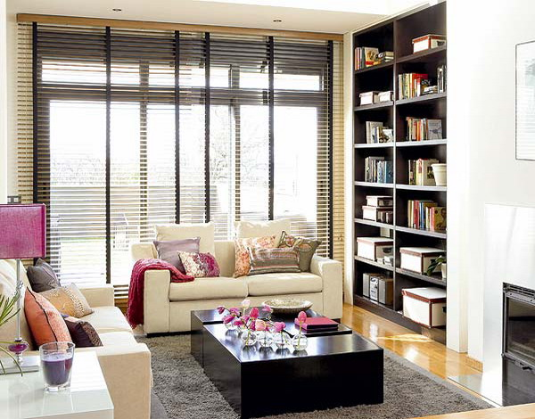 a dark built in bookcase next to the sofa is a cool idea to store books without problems and it doesn't take your floor space