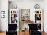 two refined vintage bookcases painted white are nice to store books with style, and loungers finish off this space