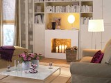 a large bookcase built-in over the faux fireplace is a cool and functional idea to use
