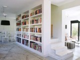 a built-in bookcase covers the whole wall and separates the staircase from the rest of the space