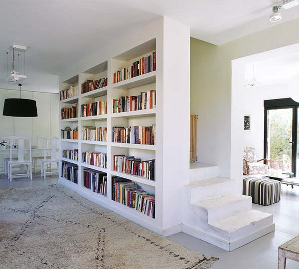 a built in bookcase covers the whole wall and separates the staircase from the rest of the space