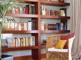 a large rich stained bookcase will spruce up a neutral space giving it a mid-century modern feel and making it bolder