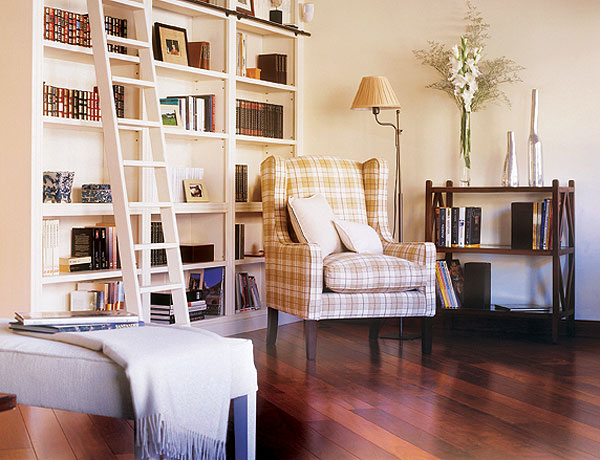 a large bookcase with an additional staircase is a cool idea, add a checked chair and some plants and a cool reading nook is ready