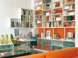 a large neutral bookcase attached to an orange statement wall is an ultra-modern idea of a library
