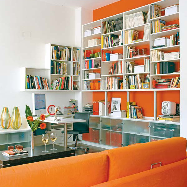 a large neutral bookcase attached to an orange statement wall is an ultra modern idea of a library