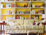 a bookcase with a sunny yellow backing is a nice and bold idea to go for, add a touch of color to your room