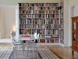 a large built-in bookcase that takes half a wall and turns the space into a library, the dining set may be used to sit on