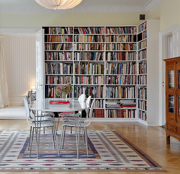 a large built in bookcase that takes half a wall and turns the space into a library, the dining set may be used to sit on