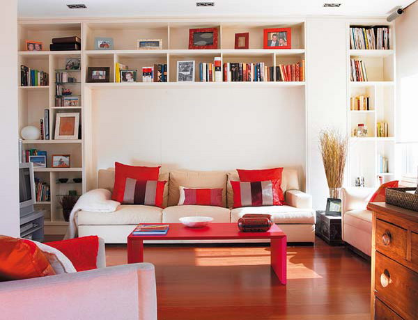 a living room with a large book storage unit over the sofa that can hold a lot of books and other stuff without taking floor space