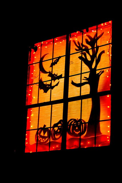 A nice Halloween window display with a tree, jack-o-lanterns, bats and half moon surrounded by string lights.